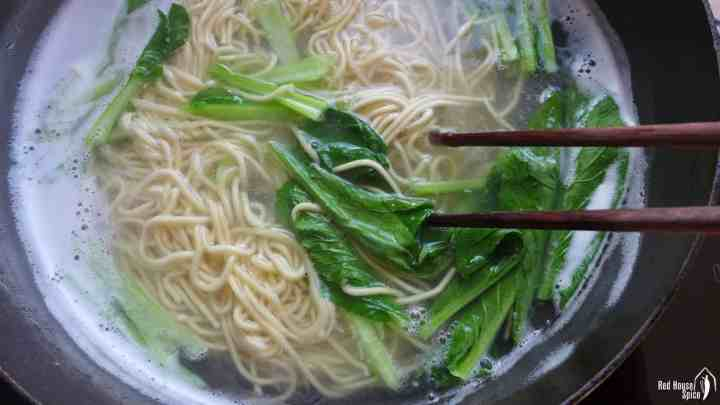 Noodles and green vegetable boiled in water.