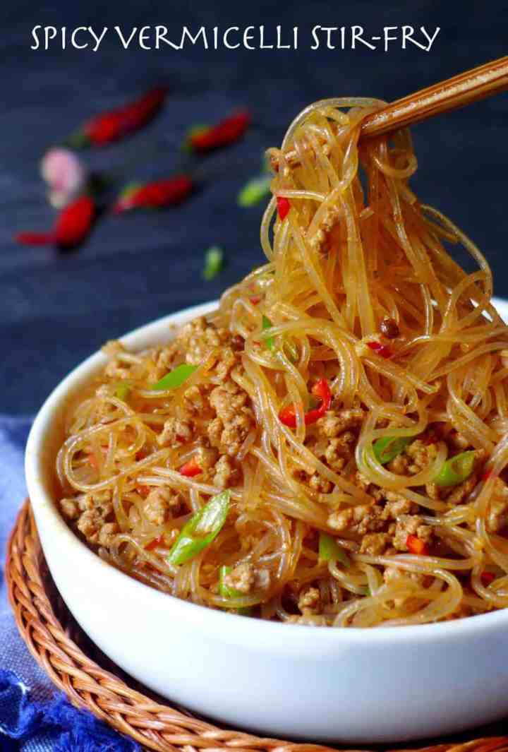 A pair of chopsticks pick up some vermicelli noodles.