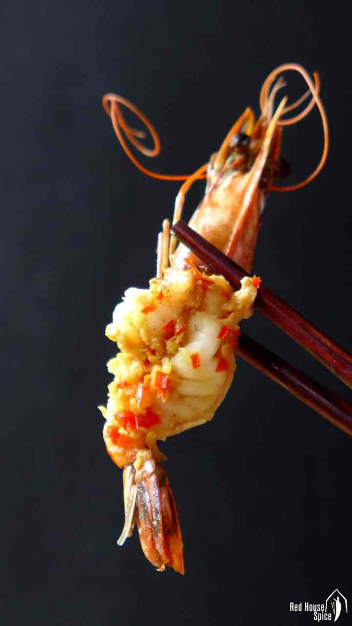 A garlic seasoned prawn held by a pair of chopsticks.
