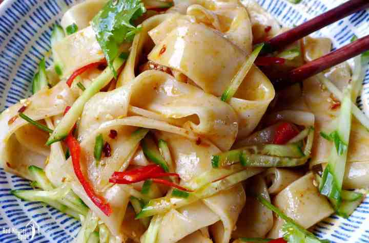 A close up shot of Liang Pi (cold skin noodles) coated with sauce and chilli oil.