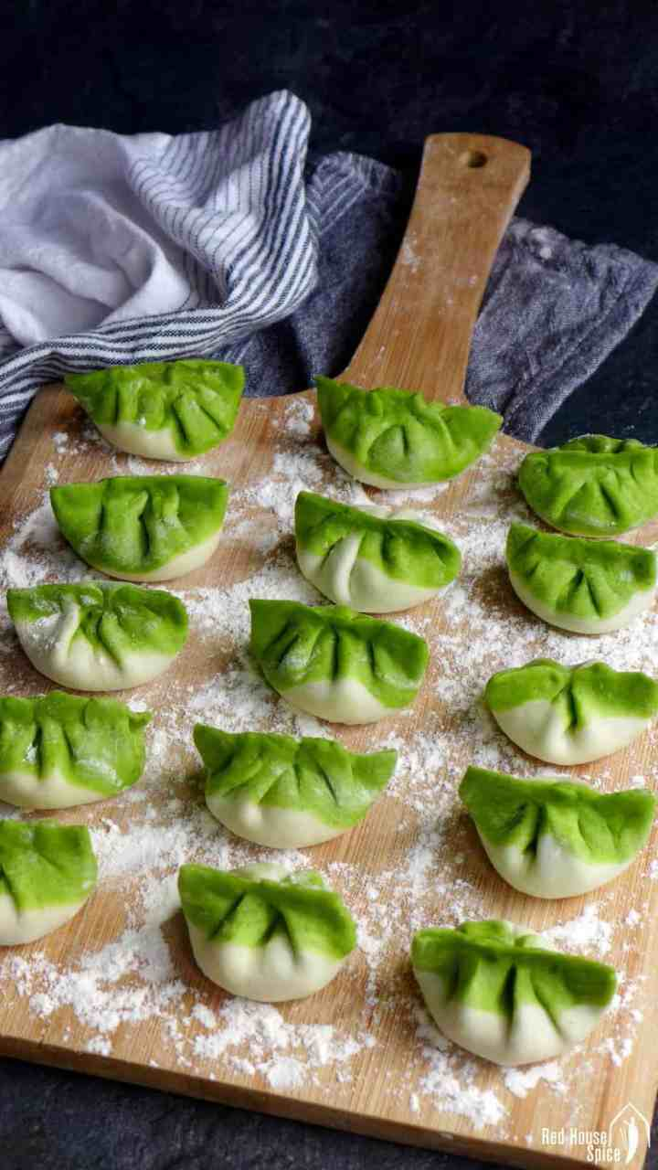 Uncooked vegetarian dumplings on a chopping board