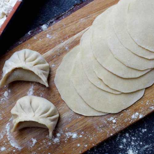 Freshly rolled dumpling wrappers and two dumplings.