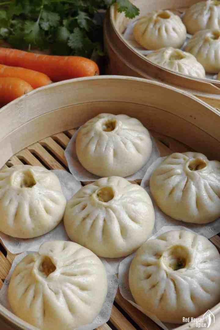 Fluffy bao buns in a bamboo steamer.