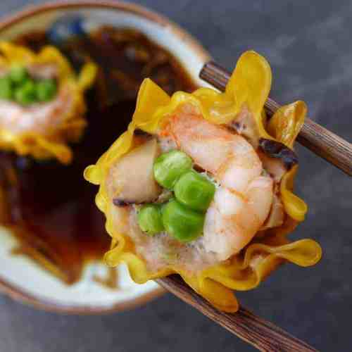 A shrimp & pork shumai held by a pair of chopsticks.