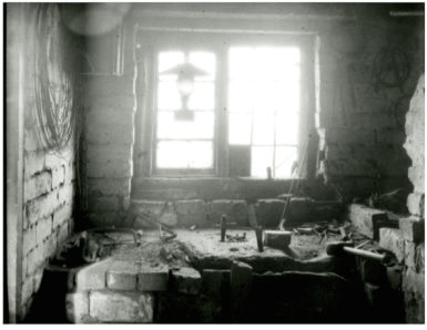 B+W image of the interioe of anAwl Blade maker's workshop Sandbank Bloxwich 1915. Tools, lamp stone block