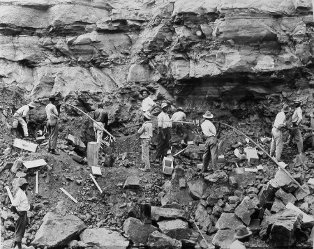 "Working with dynamite was one of the most dangerous jobs in the Canal Zone. Deaths and severe injuries to these laborers were not uncommon. In this February 1912 photograph several ""powder men"" are shown loading shot holes with dynamite to blast a slide of rock in the west bank of the Culebra Cut. (National Archives Local Identifier 185-G-154)"