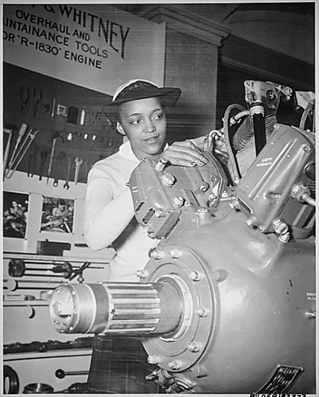 """""""Inspecting a Grumman Wildcat engine on display at the U.S. Naval Training School (WR) Bronx, NY, where she is a `boot' is WAVE Apprentice Seaman Frances Bates."""" (NAID 520638)"""