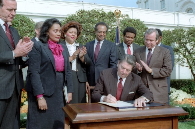 11/2/1983 President Reagan and Signing Ceremony for Martin Luther King Holiday Legislation in the rose garden with Coretta Scott King George Bush Howard Baker Bob Dole Jack Kemp Samuel Pierce Katie Hall looking on (NAID 6728680)