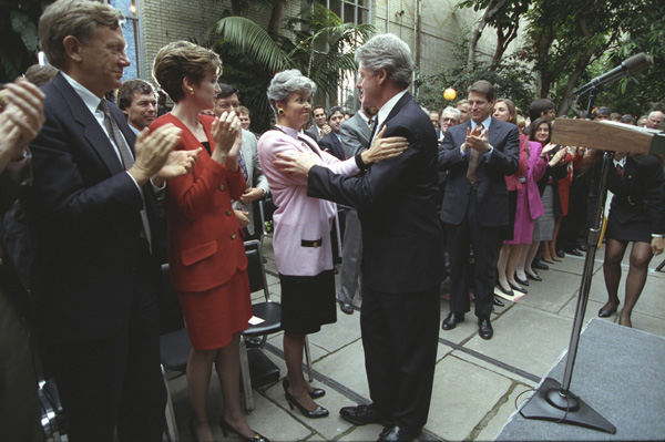 President Clinton and Secretary O'Leary embrace in front of a podium