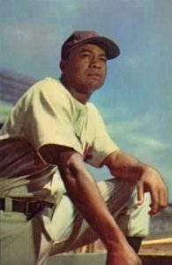 Doby with uniform and baseball cap on, kneeling on one knee and looking in the distance