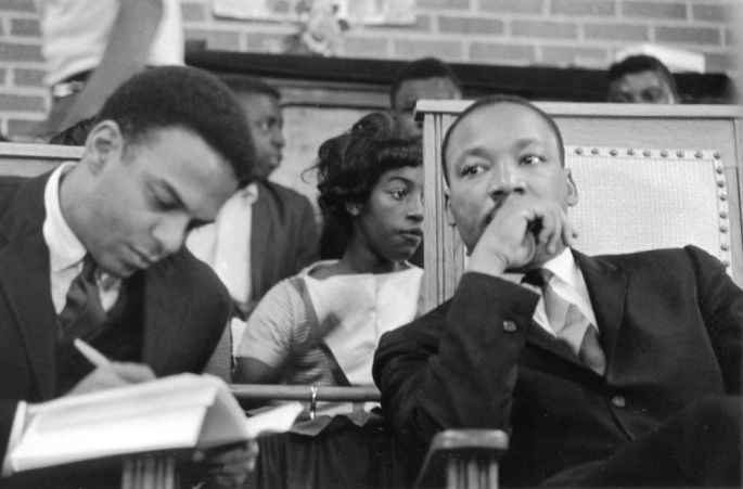 Young sitting beside Dr. King taking notes in a book