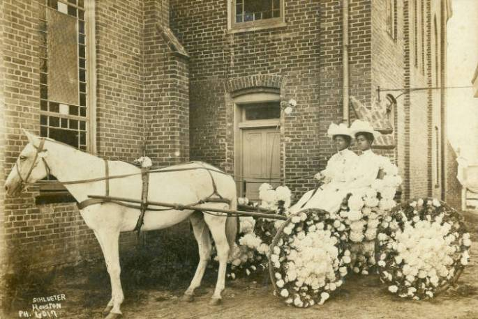 Martha Yates Jones and Pinkie Yates (both in white dresses and hats) sitting in a buggy decorated with flowers for the annual Juneteenth Celebration parked in front of Antioch Baptist Church located in Houston's Fourth Ward