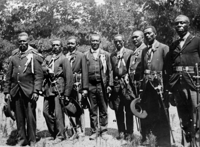 Eight men in suits with ceremonial swords on their hips