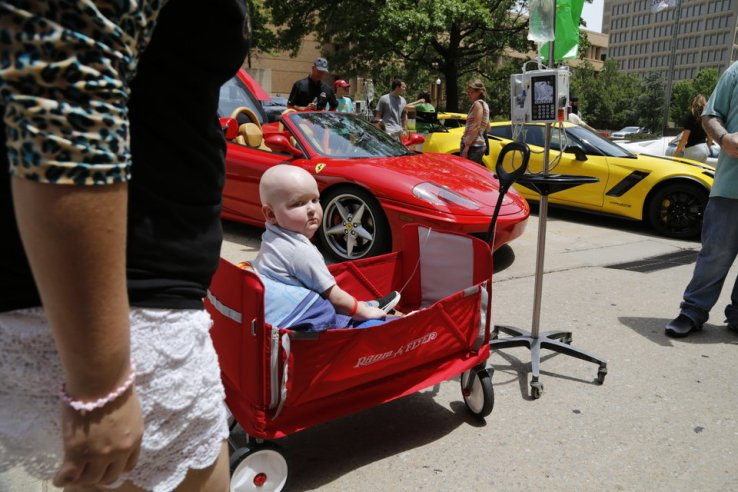 Denton Padgett, 4, came out to see the cars in his wagon, pulled by his mom and dad, Ashley and Dustin Padgett, of Chickasha. Redline4Kids is a new nonprofit that helps connect kids in the hospital with a chance to see cool cars. Photo by Jim Beckel, The Oklahoman