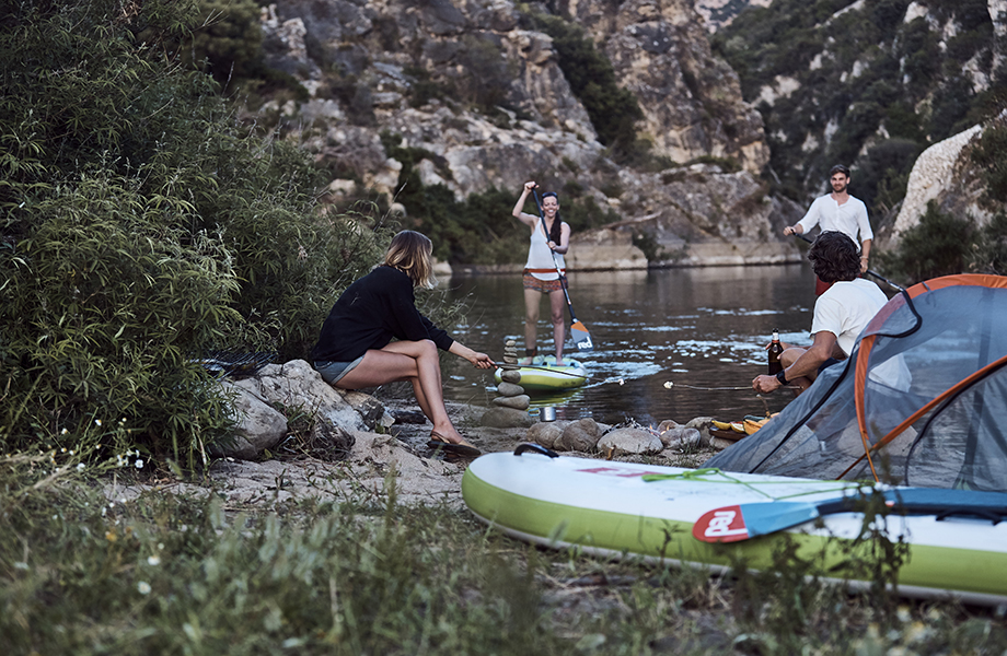 A couple paddle board into camp to meet friends on riverside