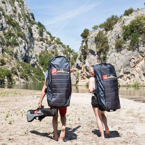 couple carrying inflatable SUP's and paddle carry bag
