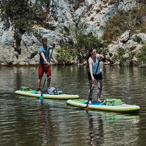 two people paddle boarding in a canyon
