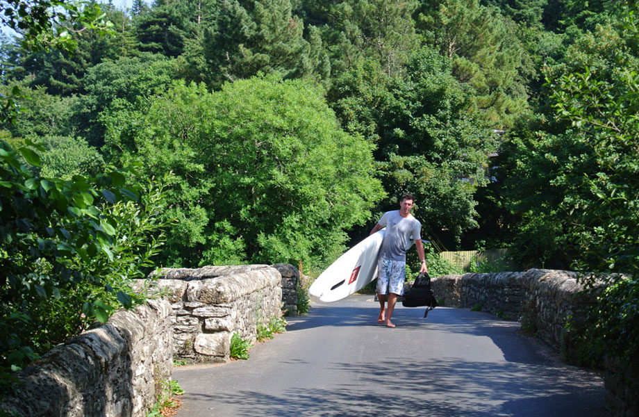 Man walks across bridge with paddle board