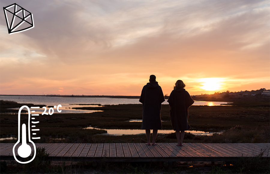 Couple stand and watch sunset