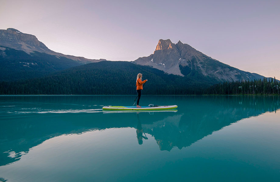Girl stands on paddle board on glassy still lake