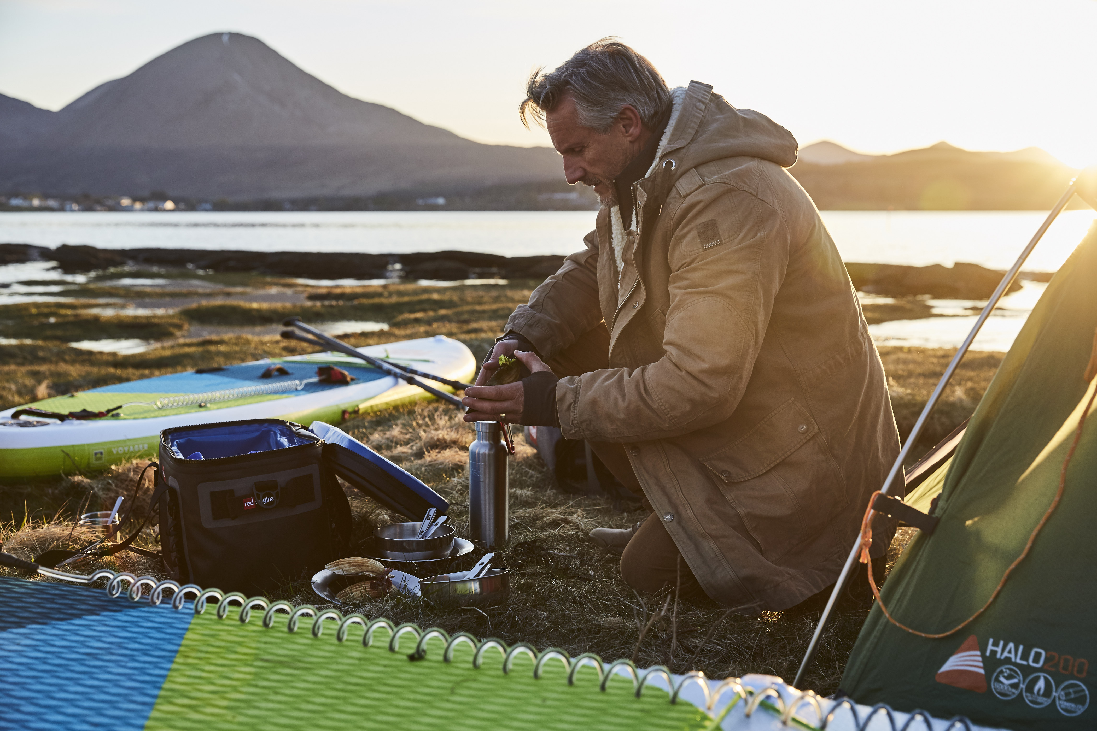 A man surrounded by camping equipment and inflatable paddle boards warms up