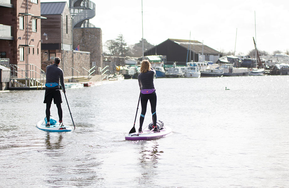 couple paddle in city harbour on inflatable SUPs