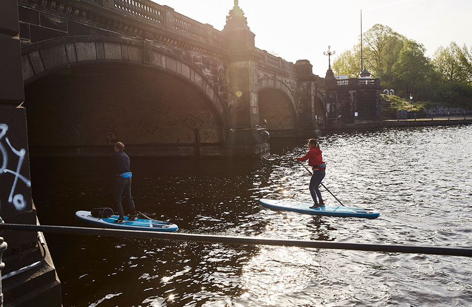 Couple paddle towards bridge on inflatable paddle boards