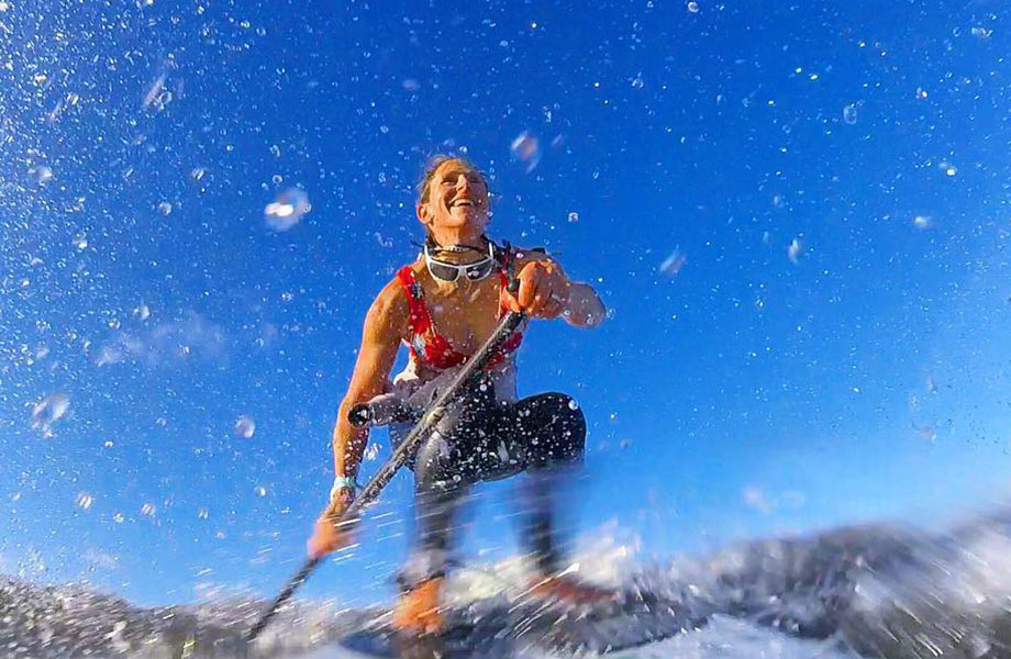 close up of woman smiling as she catches a wave with her paddle board