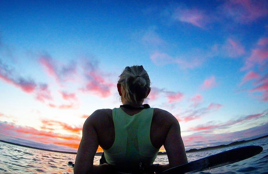 Woman looks out a sunset on her paddle board at sea