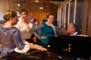 Tom Hetrick (at piano) coaches Emily Hopkins, Anne Stillwell, and Kaitrin Cunningham