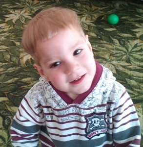 PD: George looks off-camera w/ a slight smile. He has brown eyes, blonde hair, & wears a striped sweater.