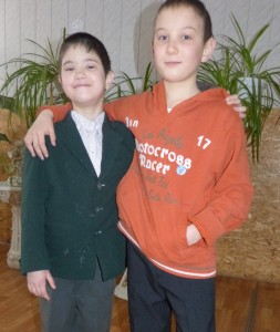 PD: Finn wears a suit jacket over a dress shirt & pants, & Sawyer wears an orange sweatshirt & dress pants. Sawyer has his arm around Finn's shoulders & both smile.