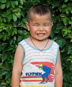 PD: Denny stands outside in front of some greenery, wearing a white tank top w/ red stripes & a cartoon Olympic skier, & a beaded necklace w/ a charm. He is smiling a big smile, squinting from the bright sun. His black hair is shaved into a mohawk style!