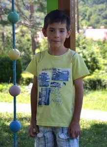 PD: Grady has dark eyes & dark hair. He stands outside, wearing a yellow t-shirt w/ plaid shorts.