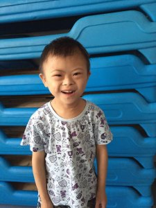 PD: Liam stands in front of stacked blue nap cots. He is wearing a white, busy-patterned shirt & a brilliant smile!