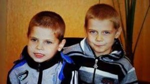 PD: Reisen & Rowan sit next to each other, wearing track jackets. Both boys have light brunette or dark blonde hair (hard to tell because of the lighting) & I believe they both have brown eyes. Both are smiling.