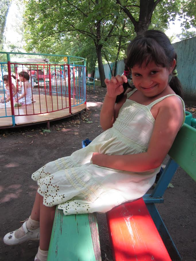 PD: Irina sits on a colourful bench, wearing a cream-coloured sundress & white shoes. She has shoulder-length, brown hair in 2 pigtails w/ bangs, smiling shyly while raising her hand to wave.