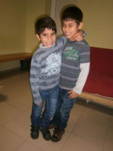 PD: Seth & Victor embrace each other, wearing long-sleeved, striped t-shirts & jeans. Both boys are smiling.