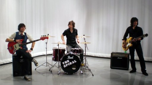 Daniel Thomas on the drums, Centre, in the band The Spiral. To right guitarist standing. To Left guitarist sitting on amp.