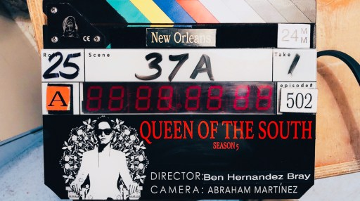 Image shows clapperboard for Queen of the South Season 5  episode number 5:02 Scene 37A, Take 1, Director: Ben Hernandez Bray Camera: Abraham Martínez. Teresa Mendoza is pictured in white, wearing sunglasses and sitting on a white throne