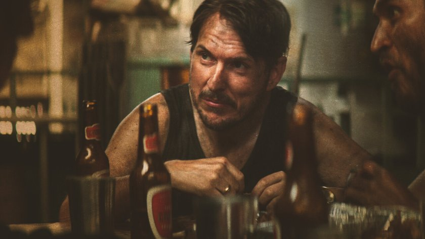 Image from The Great Heist shows Chayo (Andrés Parra) left with Maguiver (Édgar Vittorino) right. Chayo wears a black vest, they are both dirty and have beer bottle son the table in front of them.