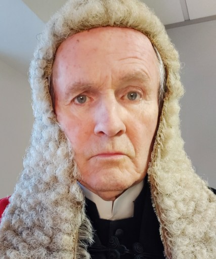 Image shows Alistair Findlay dressed as a judge with wig and gown.