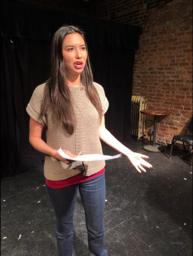 Image shows Sera-Lys McArthur during a staged reading performance fundraiser, playing Anna Mae Aquash