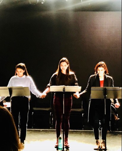 Image shows a staged reading at Yale University. Sera-Lys McArthur stands centre at lectern with Kinsale Hughes and Jen Olivares either side of her. March 2020
