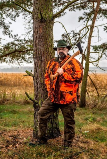 Photo shows Dan Bradford standing by a tree, wearing an orange camouflage jacket and holding an axe over his left shoulder.