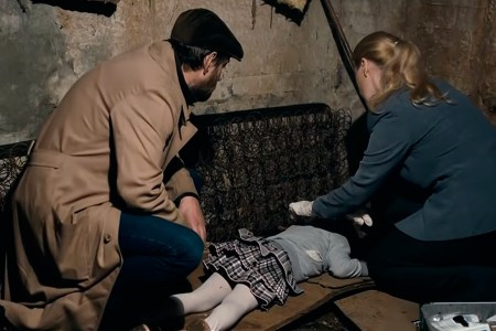 Rodion Meglin to the left crouches over the body of a young girl with a pathologist to the right in a scene from The Method