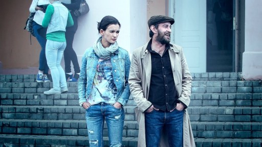 Image shows Esenya (Paulina Andreeva) left and Rodion Meglin (Konstantin Khabenskiy) right in The Method. Both have their hands in the pockets of their jeans.