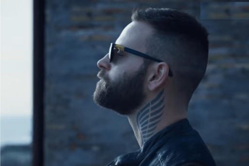 Aureliano (Alessandro Borghi) standing on the balcony of his home in Suburra: Blood on Rome. He wears sunglasses and one of his neck tattoos can be clearly seen.