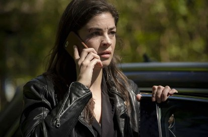Natalie Madueño as Louise Bergstein in a scene from Darkness: Those Who Kill. In this scene she is listening with her mobile phone to her ear.