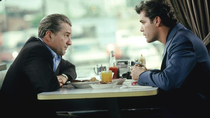 Robert De Niro as James Conway sitting in restaurant booth with Ray Liotta as Henry Hill.